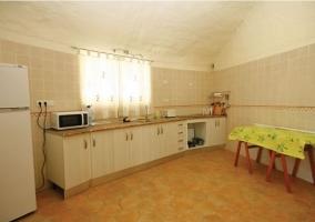 Cocina con armarios blancos y mesa auxiliar