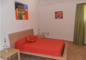 Dormitorio de matrimonio con colcha en rojo y estructura de madera