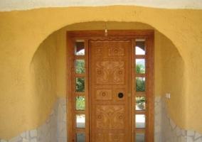 Entrada a la casa con puerta de madera y paredes amarillas