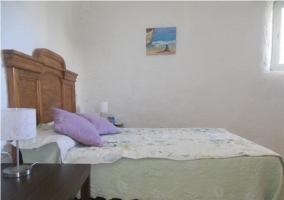 Dormitorio de matrimonio con mesillas de madera oscura