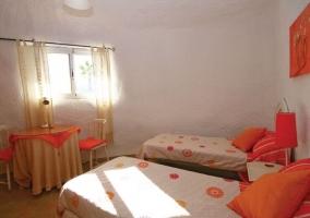 Dormitorio doble con cojines en naranja y mesilla