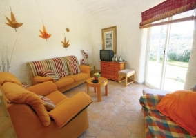Sala de estar con detalles naranjas y salida al exterior