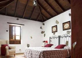 Dormitorio doble con techos altos y cabeceros de forja