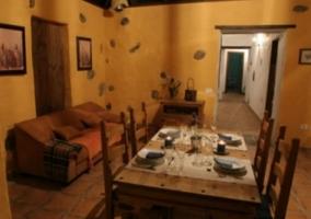 Sala de estar con mesa de madera que comunica con la cocina