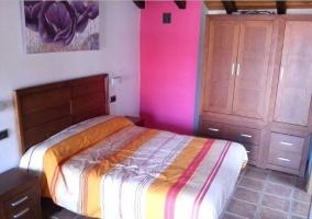 Dormitorio con cama de matrimonio y gran ventana en un lateral