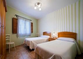 Dormitorio de matrimonio con friso de madera y colcha en blanco