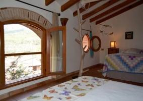 Dormitorio en la planta superior con vigas de madera