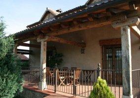 Lateral del porche y fachada de la casa