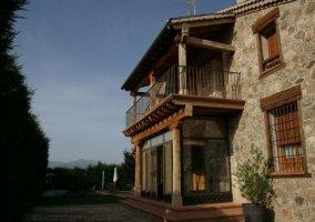 Fachada de la casa rural segoviana con porche y jardín