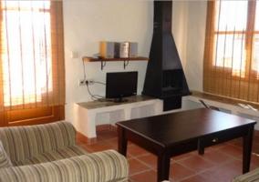 Sala de estar con chimenea frente a los sillones y mesa