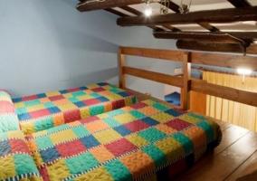 Dormitorio con un par de camas individuales y suelos de madera