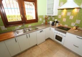 Cocina con detalles en verde y armarios en blancpo