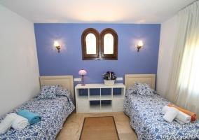 Dormitorio doble en azul con alfombra