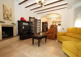 Sala de estar con la chimenea y los sillones tapizados