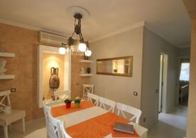 Comedor con manteles en naranja y mesa blanca