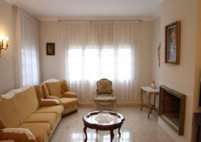 Sala de estar con sillones y una chimenea frente a ellos con cuadro