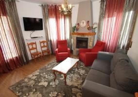 Sala de estar con chimenea y sillones grises y rojos