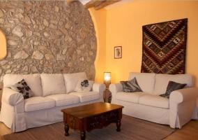 Sala de estar con pared de piedra y sillones en blanco