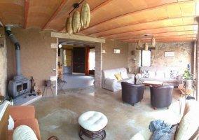 Sala de estar con estufa en una esquina y sillones