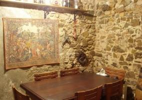 Comedor con mesa de madera y paredes de piedra