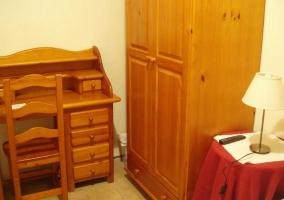 Dormitorio de matrimonio con muebles de madera y escritorio