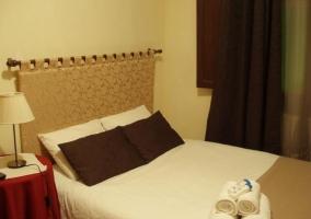 Dormitorio de matrimonio con un conjunto de toallas