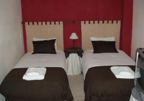 Dormitorio doble con paredes en rojo y colchas