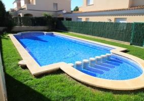 Acceso a la piscina rodeada de espacios verde