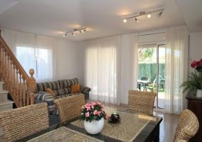 Sala de estar con mesa de comedor y centro de flores rosas