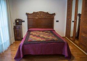 Dormitorio de matrimonio con elegante cama y cabecero