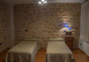 Dormitorio doble con paredes de piedra y dos camas