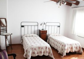 Dormitorio doble con suelos de madera y cabeceros