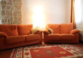 Sala de estar con alfombra en rojos y beiges