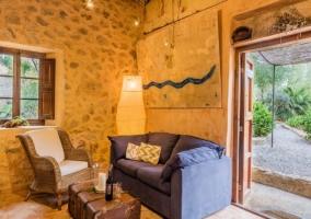 Entrada al alojamiento con fachada en piedra natural y plantas