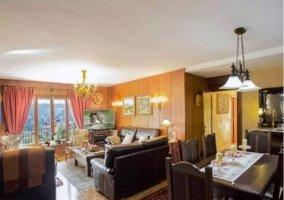 Sala de estar con sillones de cuero y chimenea en el frente