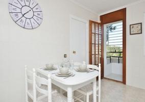 Cocina con mesa blanca y sillas