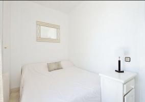Dormitorio de matrimonio con colchas y muebles en blanco