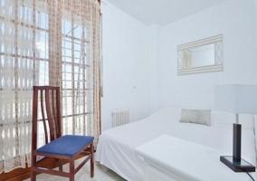 Dormitorio de matrimonio con silla de madera