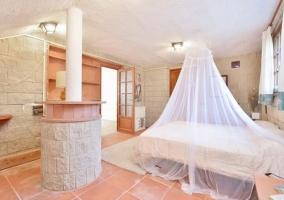 Dormitorio de matrimonio con ventana y paredes de piedra