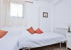 Dormitorio triple con cojines en rojo