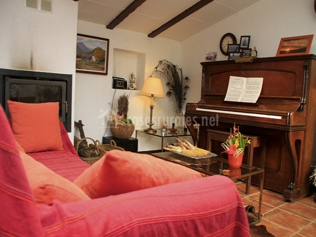 Salón con piano y chimenea