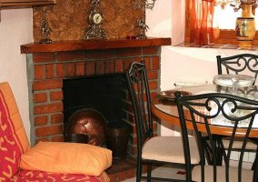 Detalle de la chimenea con mesa y sillón