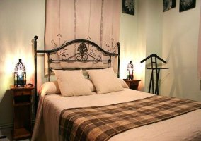 Dormitorio con cama de matrimonio y manta de cuadros