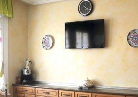 Cocina con armarios de madera y televisor
