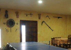 Sala de ocio con mesa de ping pong y mesa de comedor al fondo