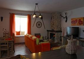 Sala de estar con sillones en naranja y chimenea