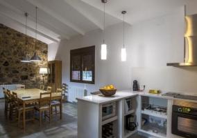 Cocina con encimera en blanco y comunicada con la sala de estar