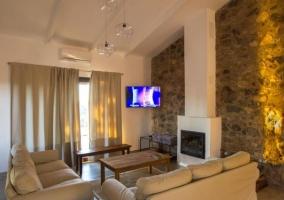 Sala de estar con paredes de piedra y chimenea