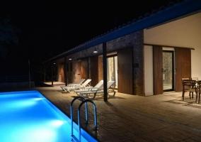 Vistas de la piscina y el porche con mesa de madera y sillas
