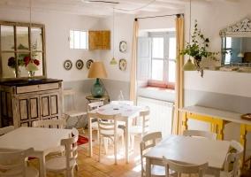 Zona de comedor con mesas y sillas blancas